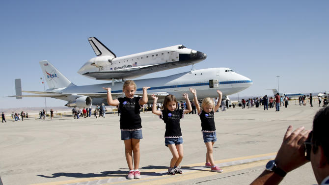 Ashely Olson, left, poses with her sisters, Alexis, center, and Alyssa in front of the Space Shuttle Endeavour at the NASA Dryden Flight Research Center at Edwards Air Force Base, Calif., Thursday, Sept. 20, 2012. Endeavour returned to its California roots after a wistful cross-country journey that paid homage to NASA workers and former Arizona Rep. Gabrielle Giffords and her astronaut husband. (AP Photo/Jae C. Hong)