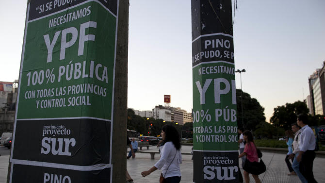 "People walk past signs reading in Spanish ""YPF, 100 percent public"" in Buenos Aires, Argentina, Thursday April 19, 2012. Argentina's government showed no signs of backing down Thursday from expropriating a Spanish company's controlling stake in YPF, Argentina's formerly state-owned energy company, shrugging off international condemnation while finding overwhelming support for the plan in congress. (AP Photo/Natacha Pisarenko)"