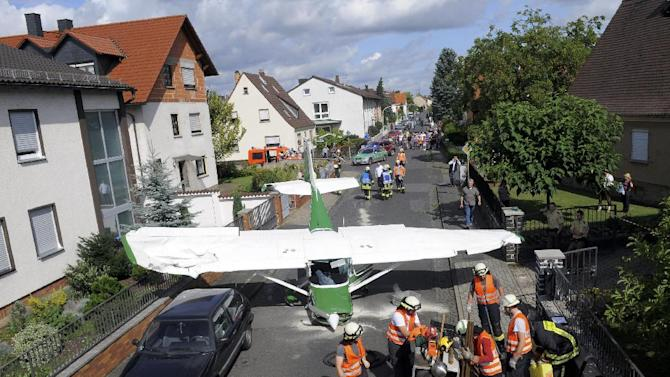 Firefighters and rescuers stand near a Cesna sport plane in the city of Stockstadt am Main, Germany Sunday Aug. 28, 2011. The pilot of the private sport plane clipped the side of a house and a lamppost while guiding his Cessna into an emergency landing on a 16-foot (5-meter) wide residential street in western Germany.  Police in Stockstadt am Main say no residents were injured and the 47-year-old pilot and his co-pilot were only lightly hurt in Sunday's crash in the densely populated area, the news agency dapd reported. They said the plane was forced down due to a technical defect, but gave no details. There was no estimate of damage. (AP Photo/dapd/ Juergen Mahnke)