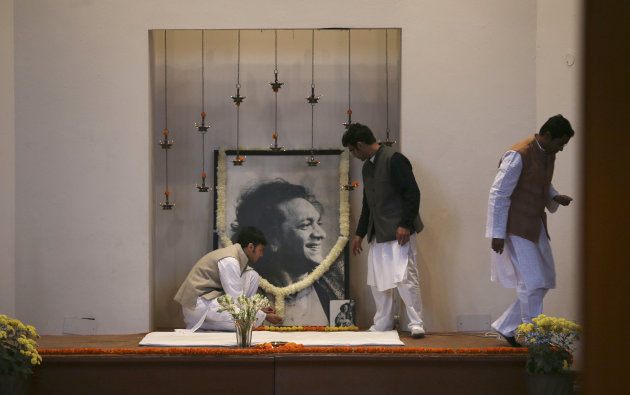 Disciples of legendary Indian sitar player Ravi Shankar put up his portrait for a prayer meeting to pay him tributes at his music center, in New Delhi, India , Wednesday, Dec. 12, 2012. Shankar, who is credited with connecting the world to Indian music, died Tuesday in San Diego, California at the age of 92. (AP Photo/Manish Swarup)