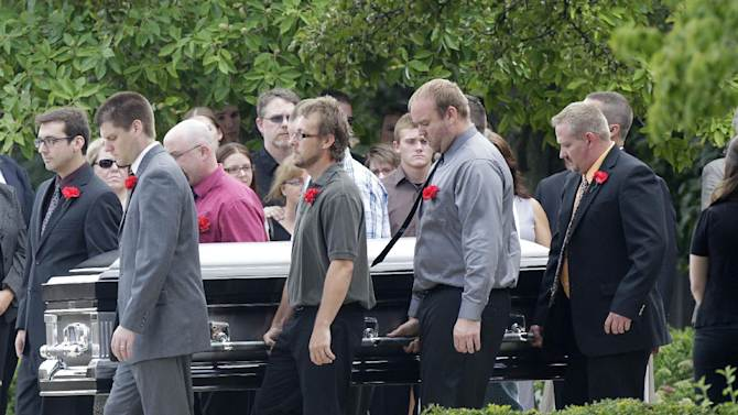 """Pallbearers carry Matt McQuinn, killed in the Aurora, Colorado movie theater shooting, from the church after his funeral Saturday, July 28, 2012, in Springfield, Ohio. McQuinn shielded his girlfriend, Samantha Yowler, from gunfire during the shooting.  Twelve people were killed and dozens were wounded in a shooting attack last Friday at a packed movie theater during a showing of the Batman movie, """"The Dark Knight Rises."""" Police have identified the suspected shooter as James Holmes, 24.  (AP Photo/Jay LaPrete)"""