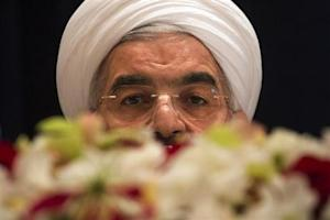 Iran's President Hassan Rouhani takes questions from journalists past a bouquet of flowers at a news conference in New York