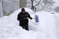 John Silver shovels between buried cars in front of his home on Third street in the South Boston neighborhood of Boston, Saturday, Feb. 9, 2013. A behemoth storm packing hurricane-force wind gusts and blizzard conditions swept through the Northeast on Saturday, dumping more than 2 feet of snow on New England and knocking out power to 650,000 homes and businesses. (AP Photo/Gene J. Puskar)