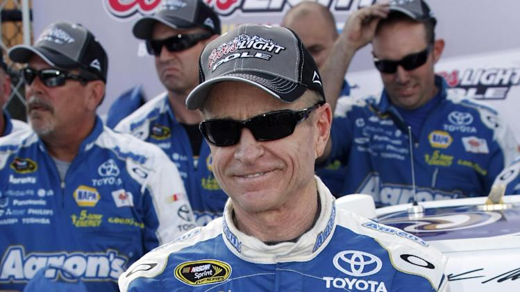 Mark Martin poses with the pole award flag after qualifications for the NASCAR Sprint Cup Series auto race at Michigan International Speedway on Friday, Aug. 17, 2012, in Brooklyn, Mich. (AP Photo/Bob Brodbeck)