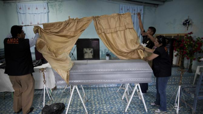 In this Aug. 17, 2012 photo, charity employees from the Funeraria del Pueblo, or People's Mortuary, prepare the wake for Marvin Adalid Membreno, a 19-year-old murder victim, inside the Prince of Peace evangelist church in Tegucigalpa, Honduras. The charities that provide the coffins, and sometimes free transportation and soft drinks to the bereaved, are run using public funds by three elected officials, two of whom are seeking the presidency and a third who is running for mayor of Tegucigalpa. The charities say the coffins are not a pitch for votes, but an important service to constituents who cannot afford a coffin.  (AP Photo/Esteban Felix)