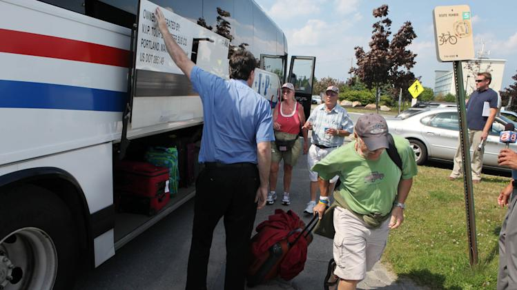 Passengers that were onboard an Amtrak train that smashed into a tractor-trailer truck arrive on a charter bus at the Portland Transportation Center Monday, July 11, 2011 in Portland, Maine. The collision killed the truck driver, injured several others and sent flames more than three stories high according to a witness and officials. (AP Photo/Joel Page)