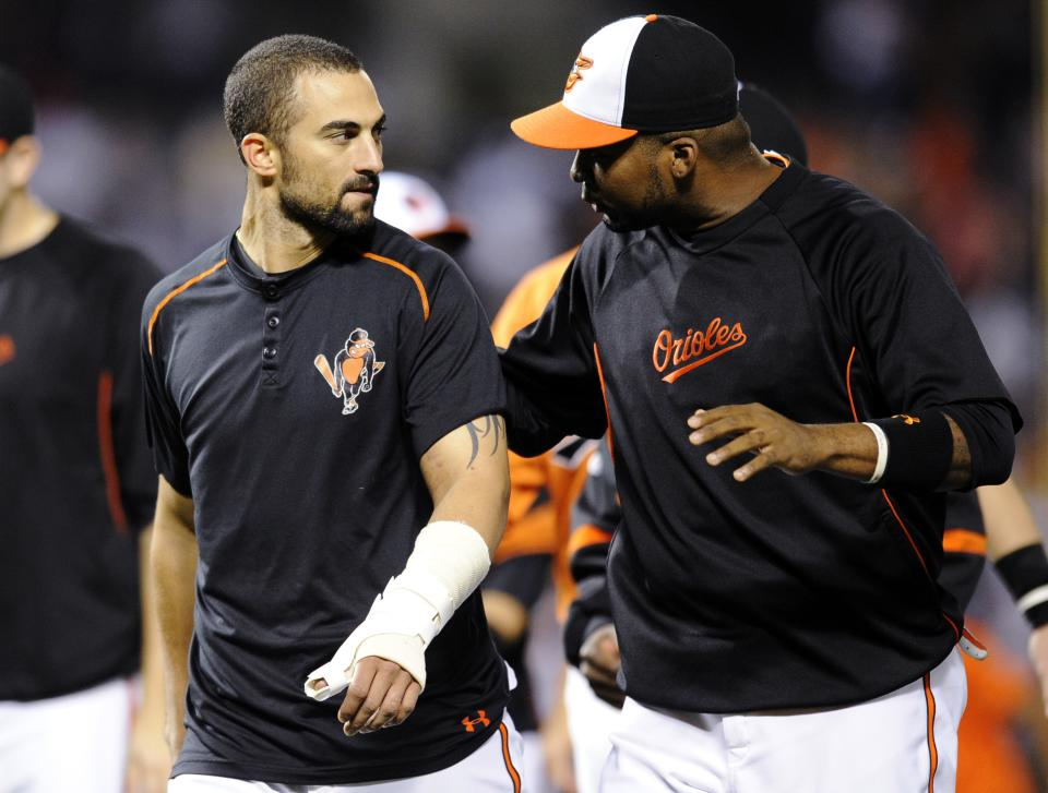 Baltimore Orioles' Nick Markakis, left, leaves the field with his thumb wrapped after celebrating their 5-4 win over the New York Yankees in a baseball game, Saturday, Sept. 8, 2012, in Baltimore. Markakis was hit by a pitch from Yankees' CC Sabathia in the fifth inning. (AP Photo/Nick Wass)