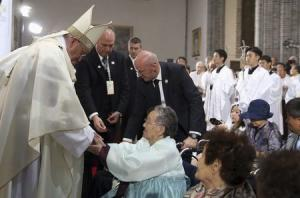"""Pope Francis consoles a woman, forced to work during the second World War as a """"comfort woman"""" for Japanese soldiers, during a Mass at Seoul's Myeongdong Cathedral"""