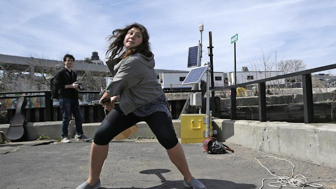 Women's division winner 18-year-old Nada Zimmermann of Innsbruck, Austria, prepares to hurl a banjo into a heavily polluted New York waterway during the fifth annual Brooklyn Folk Festival's Gowanus Banjo Toss, Sunday, April 19, 2015, in the Brooklyn borough of New York. Zimmermann won a new banjo for throwing the instrument a record-setting 67-feet. (AP Photo/Kathy Willens)