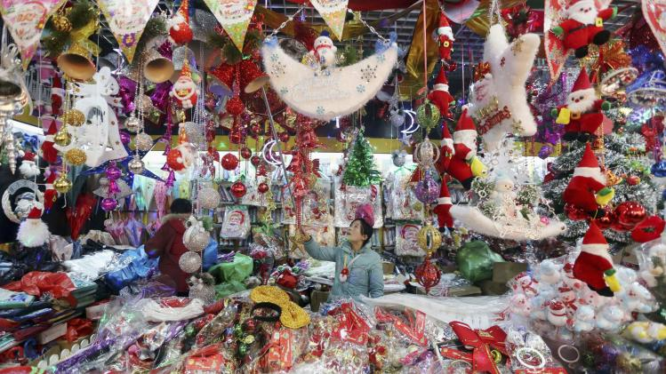 A vendor arranges Christmas products at her booth in Huaibei