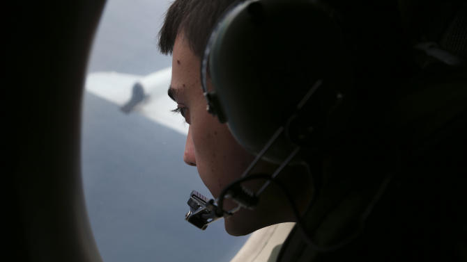 FILE - In this March 22, 2014 file photo, Sgt. Matthew Falanga on board a Royal Australian Air Force AP-3C Orion, search for the missing Malaysia Airlines flight MH370 in southern Indian Ocean, Australia. Not one object has been recovered from the missing airliner that Malaysian officials are now convinced plunged into the southern Indian Ocean 17 days ago. Some of the pieces are likely 3,500 meters (11,500 feet) underwater. Others are bobbing in a fickle system of currents that one oceanographer compares to a pinball machine. And by now, they could easily be hundreds of kilometers (miles) away from each other. (AP Photo/Rob Griffith, File)