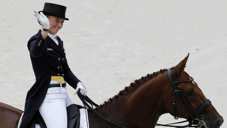 Germany's Lutkemeier, riding D'Agostino FRH, waves during the Individual Dressage Grand Prix Competition at the World Equestrian Games at the d'Ornano stadium in Caen
