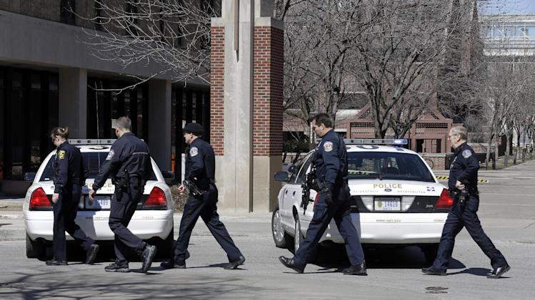 Indianapolis Metropolitan Police officers search the campus Indiana University-Purdue University Indianapolis Campus in Indianapolis, Tuesday, March 19, 2013.  Campus Police reported that a female student called  around 12:30 p.m. Tuesday after seeing a man wearing a long brown coat and carrying what looked like a long gun near a nursing building. (AP Photo/Michael Conroy)