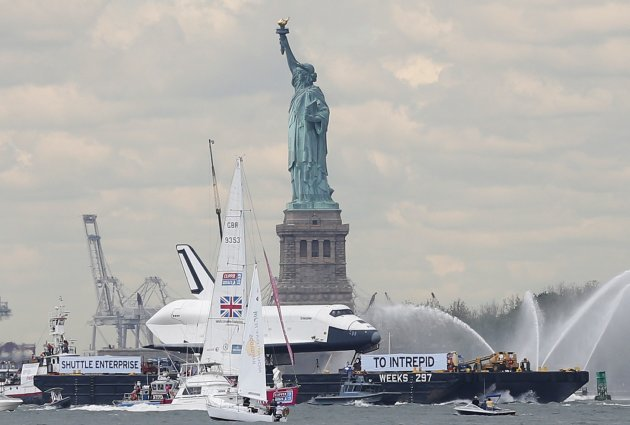 The Space Shuttle Enterprise, passes the Statue of Liberty as it rides on a barge in New York harbor
