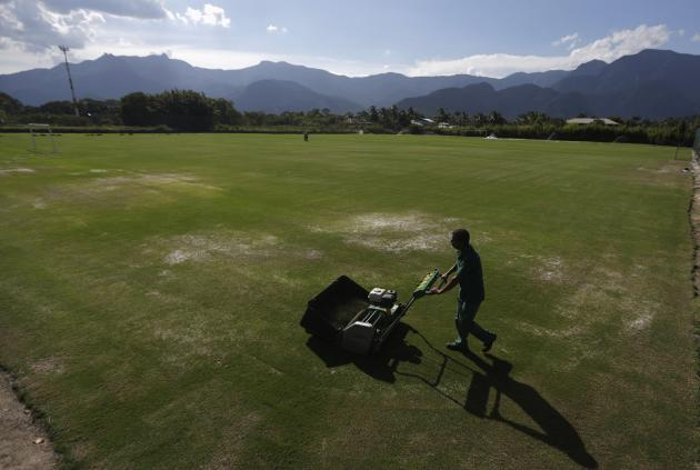 A man works on the soccer field at Portobello Resort, where the Italy soccer team will be based during the 2014 World Cup, in Mangaratiba