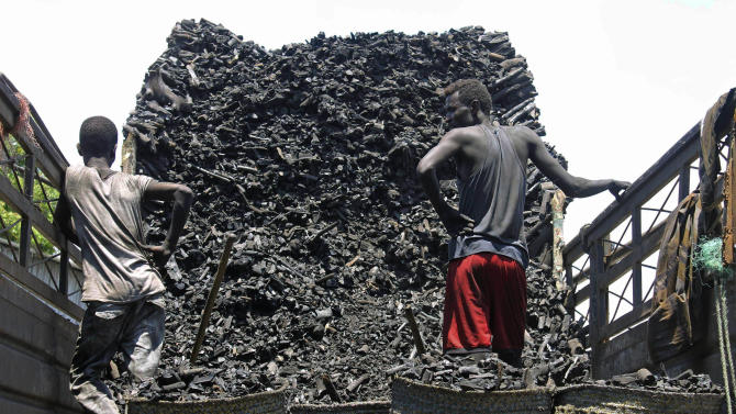 """In this photo of Tuesday Oct. 30, 2012, Somali porters  offload charcoal from a truck  at a charcoal market in Mogadishu, Somali . Thousands of sacks of dark charcoal sit atop one another in Somalia's southern port city of Kismayo, an industry once worth some $25 million dollar a year to the al-Qaida-linked insurgents who controlled the region.  The good news sitting in the idle pile of sacks is that al-Shabab militants can no longer fund their insurgency through the illegal export of the charcoal. Kenyan troops late last month invaded Kismayo and forced out the insurgents, putting a halt to the export of charcoal, a trade the U.N. banned earlier this year in an effort to cut militant profits. The loss of the charcoal trade """"will cut a major source of revenue and thus will have a detrimental effect on their operational capacity to carry out large scale attacks,"""" Mohamed Sheikh Abdi, a Somali political analyst, said of al-Shabab.  But the flip side to the charcoal problem is that residents who made their living from the trade no longer are making money, a potentially tricky issue for the Kenyan troops who now control the region. (AP Photo/Farah Abdi Warsameh)"""