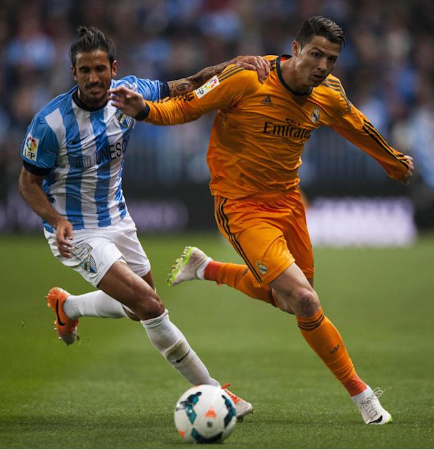 Real Madrid's Cristiano Ronaldo, right, duels for the ball against CF Malaga's Marcos Alberto Angeleri, left, during a Spanish La Liga soccer match at La Rosaleda stadium in Malaga, Spain, Sat