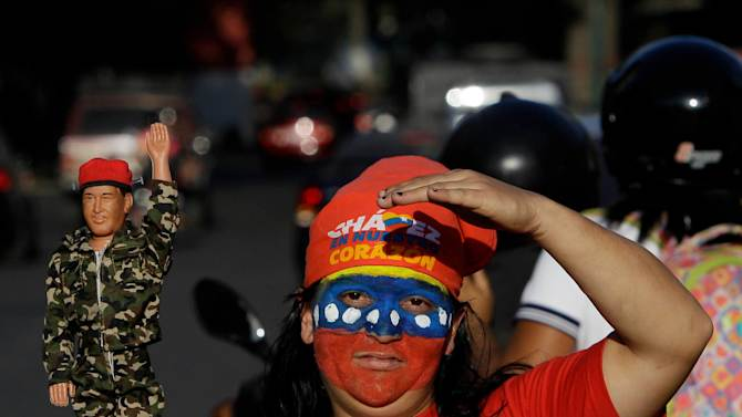 A woman, with her face painted with the colors of the Venezuelan flag, holds up a doll depicting Venezuela's President Hugo Chavez outside the military hospital in Caracas, Venezuela, Monday, Feb. 18, 2013. Chavez returned to Venezuela early Monday after more than two months of treatment in Cuba following cancer surgery, his government said, triggering street celebrations by supporters who welcomed him home while he remained out of sight at Caracas' military hospital. (AP Photo/Fernando Llano)
