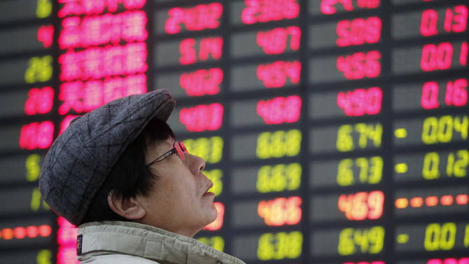An investor looks at the stock price monitor at a private securities company Wednesday, Feb. 6, 2013, in Shanghai, China. Asian shares rose Wednesday as Japan's benchmark surged to its highest level since Sept. 2008 though wariness over corporate earnings pulled European indexes lower in early trading. (AP Photo)