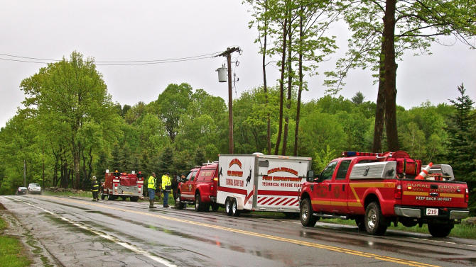 Emergency vehicles sit parked along the road outside Granny's Ice Cream Shanty, a second command post in Ephratah, N.Y., Saturday, May 25, 2013, as the search for the pilot of a downed Angel Flight out of Massachusetts continues. The twin engine light plane plane carrying two passengers and the pilot crashed in a wooded are in upstate New York on Friday. Angel Flight is a nonprofit group that arranges free air transportation for sick patients from volunteer pilots. (AP Photo/The Daily Gazette, Bethany Bump)