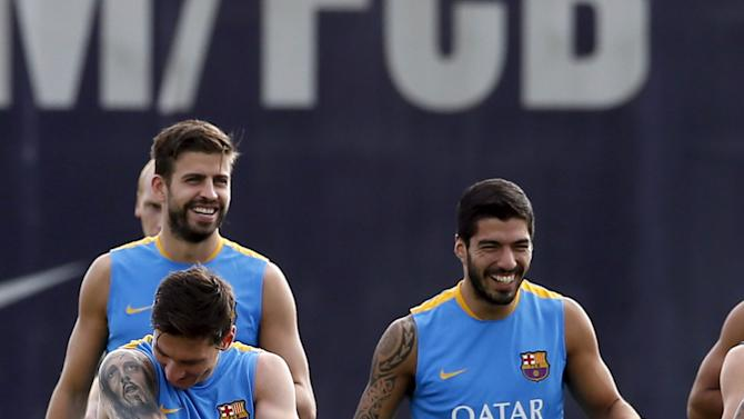 Barcelona's soccer players Lionel Messi, Gerard Pique and Luis Suarez attend a training session at Joan Gamper training camp