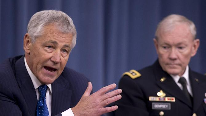 In this April 10, 2013, photo, Defense Secretary Chuck Hagel, left, accompanied by Joint Chiefs Chairman Gen. Martin Dempsey, speaks at a news conference at the Pentagon in Washington, about the fiscal year 2014 defense budget. (AP Photo/Carolyn Kaster)