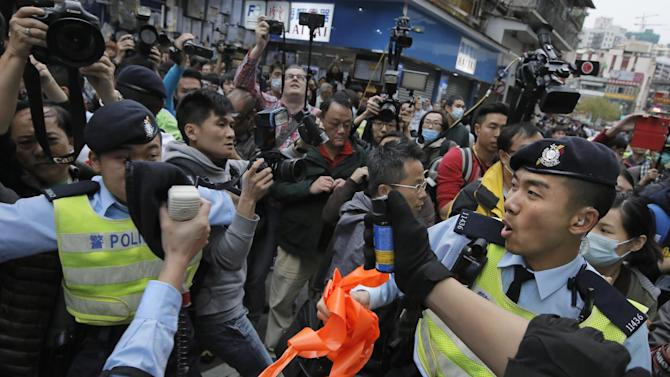 In this Sunday, March 1, 2015 photo, police officers try to control the confrontation between activists demonstrating against the mainland Chinese shoppers and local villagers at a suburban district of Yuen Long in Hong Kong. Eighteen years after this world financial hub returned from colonial British control to Chinese rule, many say they feel more alienated and less trusting than ever of the central Chinese government and even the people visiting from across the border. The complaints range from the small to the sweeping, from the perceived rudeness of Chinese tourists to fears that leaders in Beijing are sabotaging the freedoms and rule of law that have long distinguished Hong Kong from the rest of China. (AP Photo/Vincent Yu)