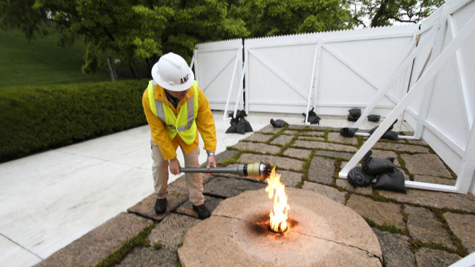 This handout photo provided by Arlington National Cemetery, taken April 29, 2013, shows Randy Barton, an Arlington National Cemetery engineering technician, lighting a torch from the John F. Kennedy Eternal Flame at the cemetery in Arlington, Va. The torch was used to transfer the flame to a temporary burner while the permanent flame undergoes repair and upgrade work to install new burners, a new igniter as well as new gas and air lines. The eternal flame at the gravesite of former President John F. Kennedy is undergoing repairs at the cemetery. Before the repairs began, workers used a torch to carry the flame and pass it to a temporary burner that will be visible to tourists at the site while work is underway. Cemetery officials say the work will take about three weeks and should be completed by late May, when the flame will be passed back to the original site. A temporary flame was used from the time of Kennedy's November 1963 funeral until the permanent flame was established in 1967. Officials said repairs are needed after more than four decades of use and will include new gas lines and more efficient burners. (AP Photo/Patrick Bloodgood, US Army, Arlington National Cemerery)