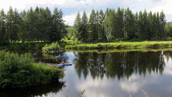In this Aug. 11, 2013 photo, paddlers move through placid waters from the P'tit Train du Nord rail trail outside Montreal, Quebec. The rail trail cuts through stands of hardwood and softwood forests, along lakes and rushing rivers, with inns and cafes along the way. (AP Photo/Calvin Woodward)