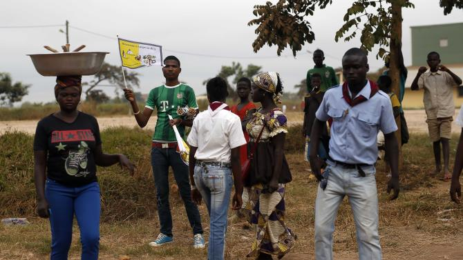 People wait outside the airport for the arrival of Pope Francis in Bangui, Central African Republic, Sunday Nov. 29, 2015. The Pope is in Africa for a six-day visit that is taking him to Kenya, Uganda and the Central African Republic. (AP Photo/Jerome Delay)