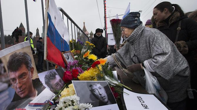 """People lay flowers next to the place where Boris Nemtsov, a charismatic Russian opposition leader and sharp critic of President Vladimir Putin, was gunned down, during a march on Friday, Feb. 27, 2015, near the Kremlin, with St, Basil Cathedral is in the background in Moscow, Russia, Sunday, March 1, 2015. Thousands converged Sunday in central Moscow to mourn veteran liberal politician Boris Nemtsov, whose killing on the streets of the capital has shaken Russia's beleaguered opposition. They carried flowers, portraits and white signs that said """"I am not afraid."""" (AP Photo/Alexander Zemlianichenko Jr.)"""