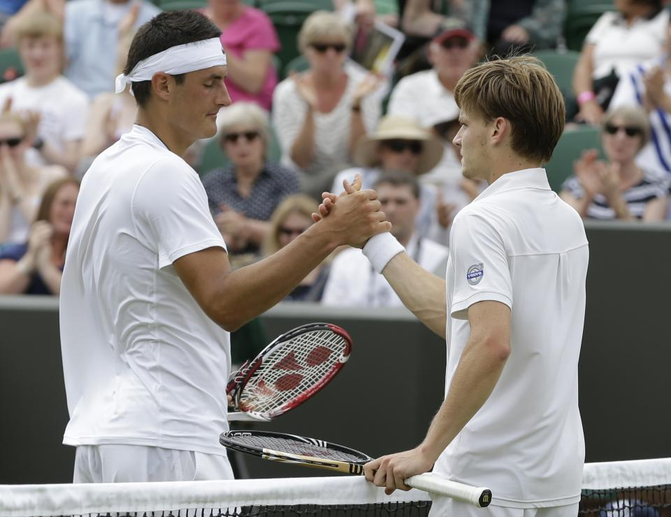 David Goffin of Belgium, right, is congratulated by Bernard Tomic of Australia following a first round men's singles match at the All England Lawn Tennis Championships at Wimbledon, England, Tuesday, June 26, 2012. (AP Photo/Alastair Grant)