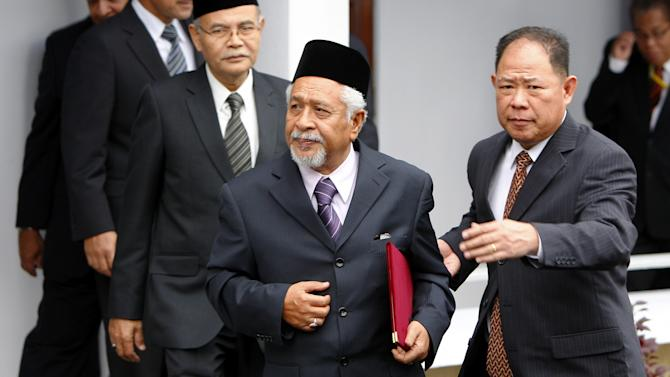 Chief of Malaysian-based National Revolution Front Hassan Taib, center, leaves after the signing ceremony of the general consensus document to launch a dialogue process for peace in the border provinces of southern Thailand, in Kuala Lumpur, Malaysia, Thursday, Feb. 28, 2013. Thai authorities and Muslim militant leaders based in neighboring Malaysia agreed Thursday to hold talks to help ease nearly a decade of unrest in southern Thailand. (AP Photo/Lai Seng Sin)