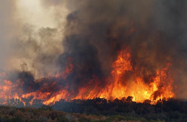 A wildfire roars through dry trees near  Possum Kingdom Lake, Texas, Wednesday, Aug. 31, 2011.   Texas and Oklahoma are in the grips of a record-setting drought, and a summer of soaring temperatures a