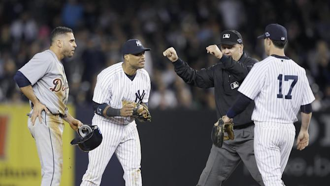 Umpire Jeff Nelson is approached by New York Yankees' Robinson Cano, left, and Jayson Nix after calling Detroit Tigers' Omar Infante safe at second base in the eighth inning of Game 2 of the American League championship series Sunday, Oct. 14, 2012, in New York. (AP Photo/Matt Slocum)