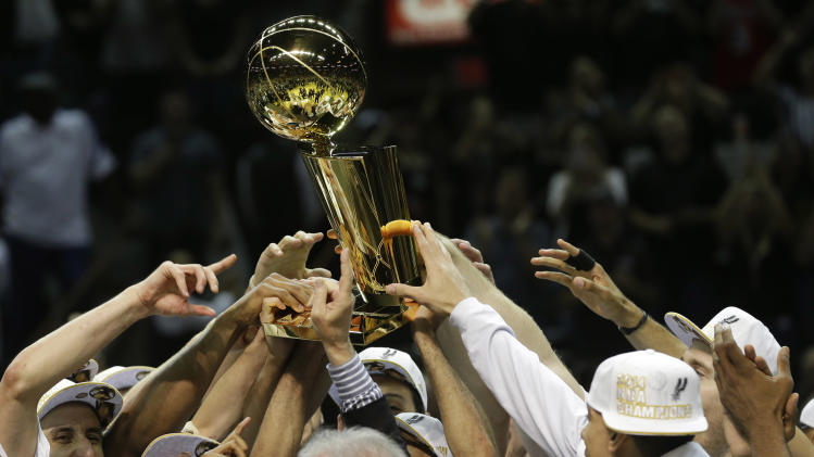 The San Antonio Spurs lift the Larry O'Brien NBA Championship Trophy after Game 5 of the NBA basketball finals on Sunday, June 15, 2014, in San Antonio. The Spurs won the NBA championship 104-87. (AP Photo/David J. Phillip)