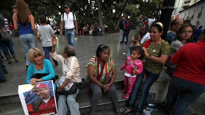 "Supporters of Venezuela's President Hugo Chavez, one of them holding a sign with an image of him, gather outside of the National Assembly during the  state-of-the-nation address in Caracas, Venezuela, Tuesday, Jan. 15, 2013. Venezuela's Vice President Nicolas Maduro submitted the report in writing from ailing President Hugo Chavez, who is receiving treatment in Cuba after undergoing his fourth cancer surgery. Opposition politicians had argued that lawmakers should have postponed the annual speech because Chavez was supposed to deliver it. The sign reads in Spanish ""Go ahead commander."" (AP Photo/Fernando Llano)"