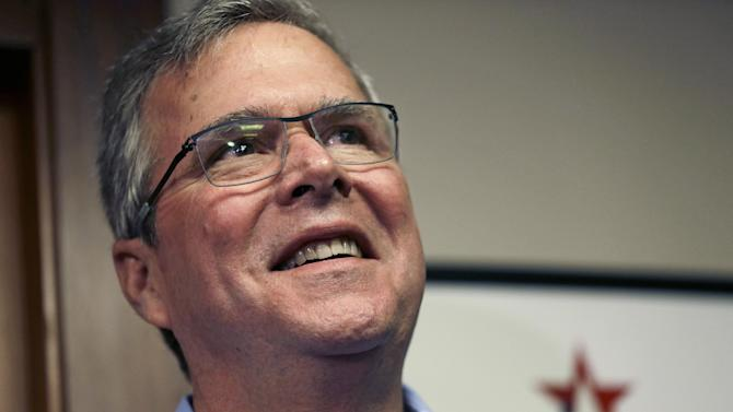 "In this April 17, 2015, photo, former Florida Gov. Jeb Bush smiles while speaking to reporters after a ""Politics and Eggs"" event, a breakfast fixture for 2016 presidential prospects at Saint Anselm College in Manchester, N.H. Bush is preparing to embark on an experiment in presidential politics: delegating many of the nuts-and-bolts tasks of seeking the White House to a separate political organization that can raise unlimited amounts of campaign cash. (AP Photo/Elise Amendola)"