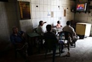 Egyptians sitting in a traditional coffee shop watch Mohamed Morsi take the oath of office in Cairo. Morsi was sworn in as Egypt&#39;s first freely elected civilian president on Saturday and formally received a transfer of power and pledge of support from the military, which has ruled since last year
