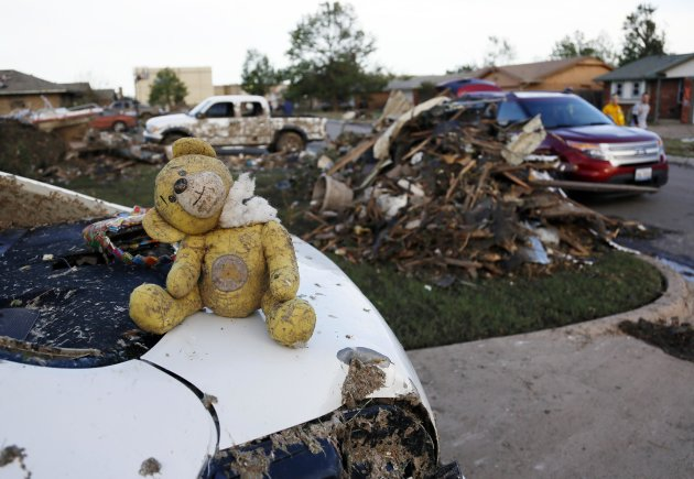 A teddy bear salvaged from the rubble of a tornado-destroyed home sits on the boot of a vehicle, in Moore