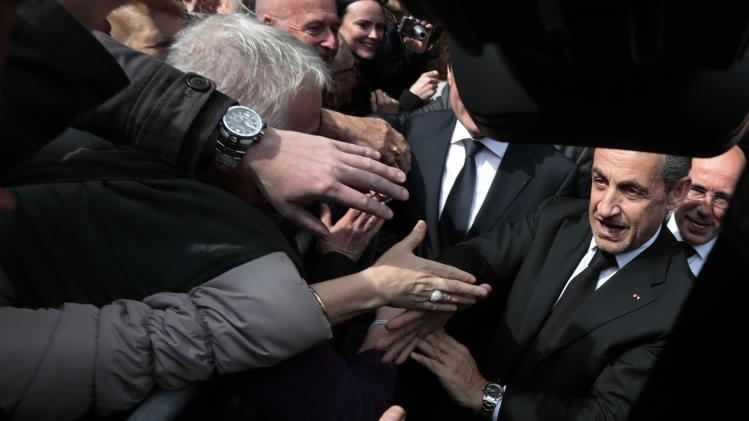 Former French President Nicolas Sarkozy shakes hands with well-wishers as he leaves following the inauguration of the Institut Claude Pompidou in Nice