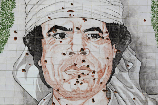 A giant portrait of Moamar Gadhafi is bullet-riddled on the wall of a building in the Bab al-Aziziyah district in Tripoli, Libya, Saturday, Aug. 27, 2011. Libyan rebels fought Saturday for control of a major supply road to the capital, seizing a border crossing with Tunisia and strengthening their hold on the oil-rich country as they hunt for Moammar Gadhafi. (AP Photo/Francois Mori)