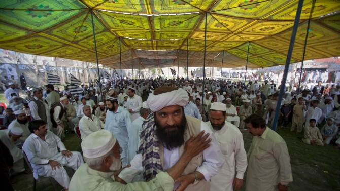"""In this Thursday, May 2, 2013 photo, Maulana Shujaul Mulk, center, pro-Taliban Jamiat-e-Ulema Islam (JUI-F), is greeted by a supporter as he arrive to address an election campaign rally in Mardan, Pakistan. Mulk is among several Pakistani Islamists and sectarian groups contesting for the country's upcoming parliamentary elections, which are divided and scattered though, they are still in a position to secure enough strength to play Pakistani establishment bid to """"hound"""" the next frail government in influencing its decisions about the U.S. forces withdrawal from Afghanistan in 2014. (AP Photo/Anjum Naveed)"""