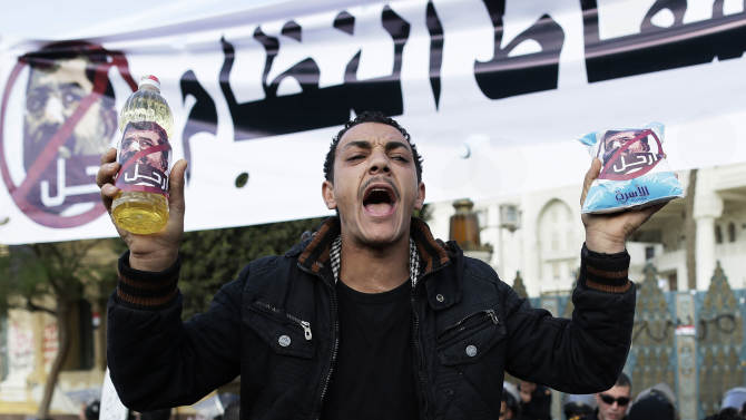 """An Egyptian protester holds up a battle of oil and a bag of sugar as he chants anti-Muslim Brotherhood and Egyptian President Mohammed Morsi slogans outside the presidential palace under a banner with a defaced picture of president Mohammed Morsi and Arabic that reads """"the people want  to bring down the regime,""""  in Cairo, Egypt, Saturday, Dec. 8, 2012. Egypt's military has warned of 'disastrous consequences' if the political crisis gripping the country is not resolved through dialogue. Arabic sign on the battle and bag read, """"leave.""""(AP Photo/Hassan Ammar)"""