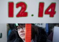 Cheryl Sayles-Palumbo of Milford, Conn. holds a sign reading the date of the Sandy Hook Elementary School shooting during a rally at the Capitol in Hartford, Thursday, Feb. 14, 2013. Thousands of people turned out to call on lawmakers to toughen gun laws in light of the December elementary school shooting in Newtown that left 26 students and educators dead. (AP Photo/Jessica Hill)