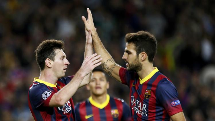 Barcelona's Messi is congratulated by team mate Fabregas after scoring his second goal against AC Milan during their Champions League soccer match in Barcelona