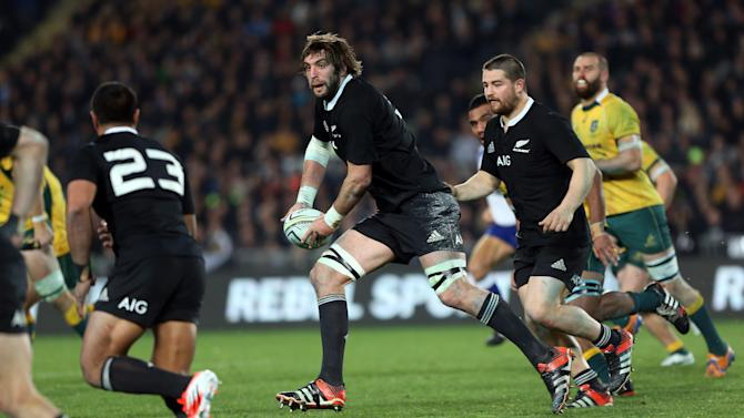 New Zealand's Sam Whitelock (C) passes the ball during the rugby union Test match against the Wallabies at Eden Park on August 23, 2014