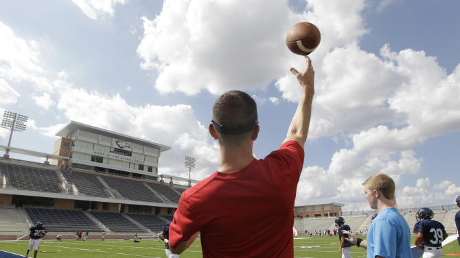 Football coach Jeff Fleener tosses a football to players during practice at the new $60 million football stadium at Allen High School Tuesday, Aug. 28, 2012 in Allen, Texas.  Allen High School northeast of Dallas christens the stadium Friday night with a matchup against defending state champion Southlake Carroll. While other school districts are struggling to retain teachers and keep classroom sizes down, Allen voters approved a $119 million bond issue that pays for the stadium and other district facilities. (AP Photo/LM Otero)