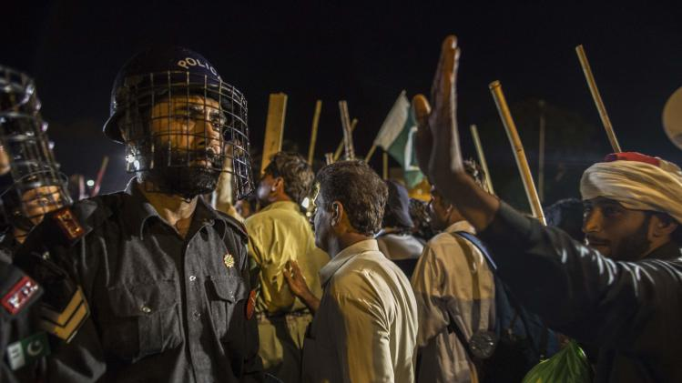 A riot police officer looks on as supporters of Tahir ul-Qadri move towards Prime Minister's house during the Revolution March in Islamabad