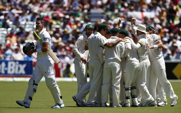 England's Pietersen walks off the field after his dismissal, as the Australian team celebrates, during the third day of the second Ashes test cricket match in Adelaide